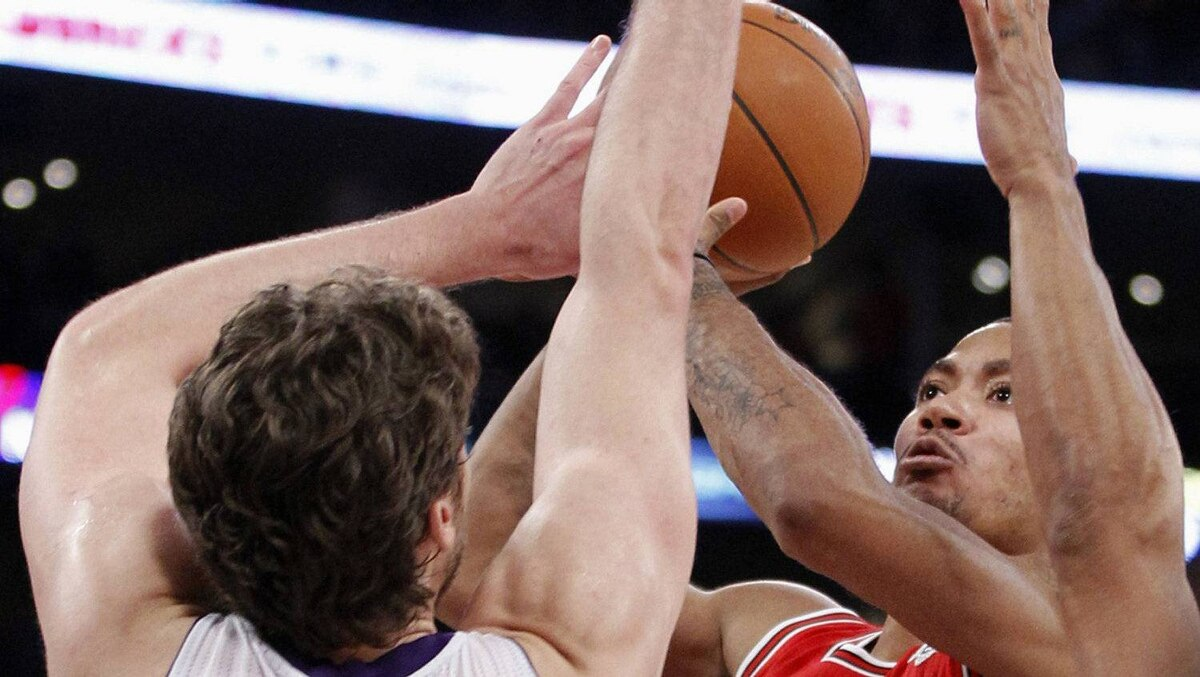 Chicago Bulls' Derrick Rose (R) makes a go ahead basket with 4.8 seconds left over Los Angeles Lakers' Pau Gasol of Spain during the second half of an NBA basketball game in Los Angeles December 25, 2011. The Bulls won 88-87. REUTERS/Danny Moloshok