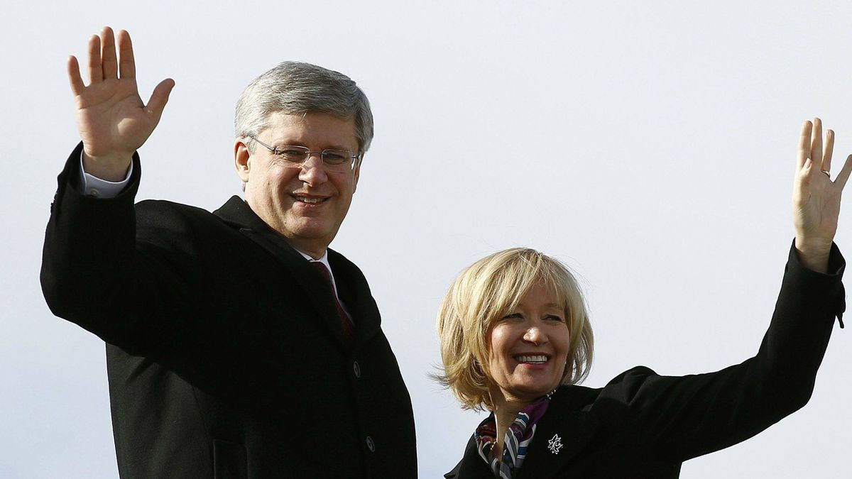 Canada's Prime Minister Stephen Harper and his wife Laureen wave while boarding their plane before departing for China, in Ottawa, Monday.