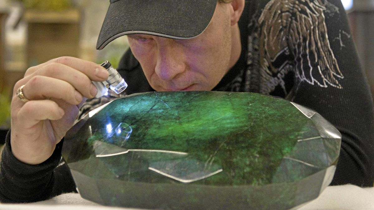 """Regan Reaney, owner of the the world's largest emerald looks over the gem at the Western Star Auction House in Kelowna, British Columbia January 26, 2012. The 57,500 carat emerald, named """"Teodora"""", which weighs 11.5 kg (25.35 lb) was mined in Brazil and cut in India. The stone will be publicly auctioned this weekend."""