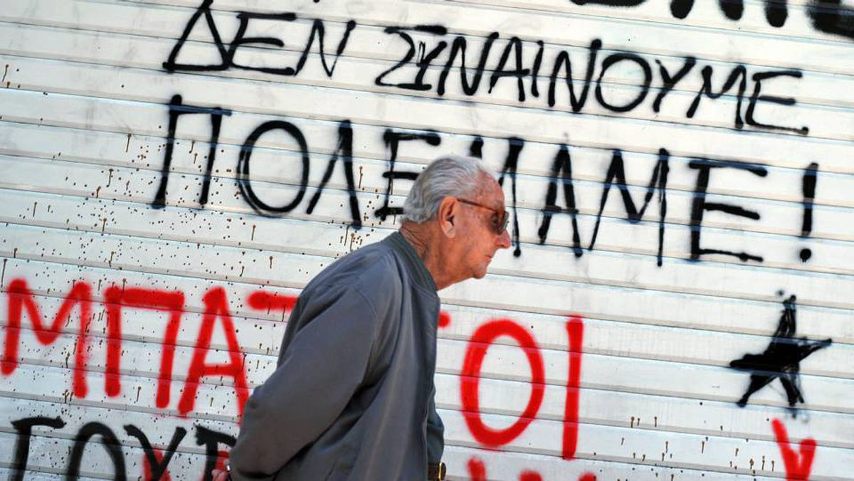 A man walks in front of a graffiti-covered wall in downton Athens on Sunday. The anti-austerity-plan slogan reads, 'We do not agree - We have war.'