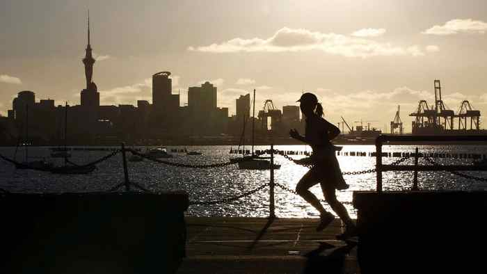 A jogger runs along the seawall in Auckland September 26, 2011, with the city skyline in the background.