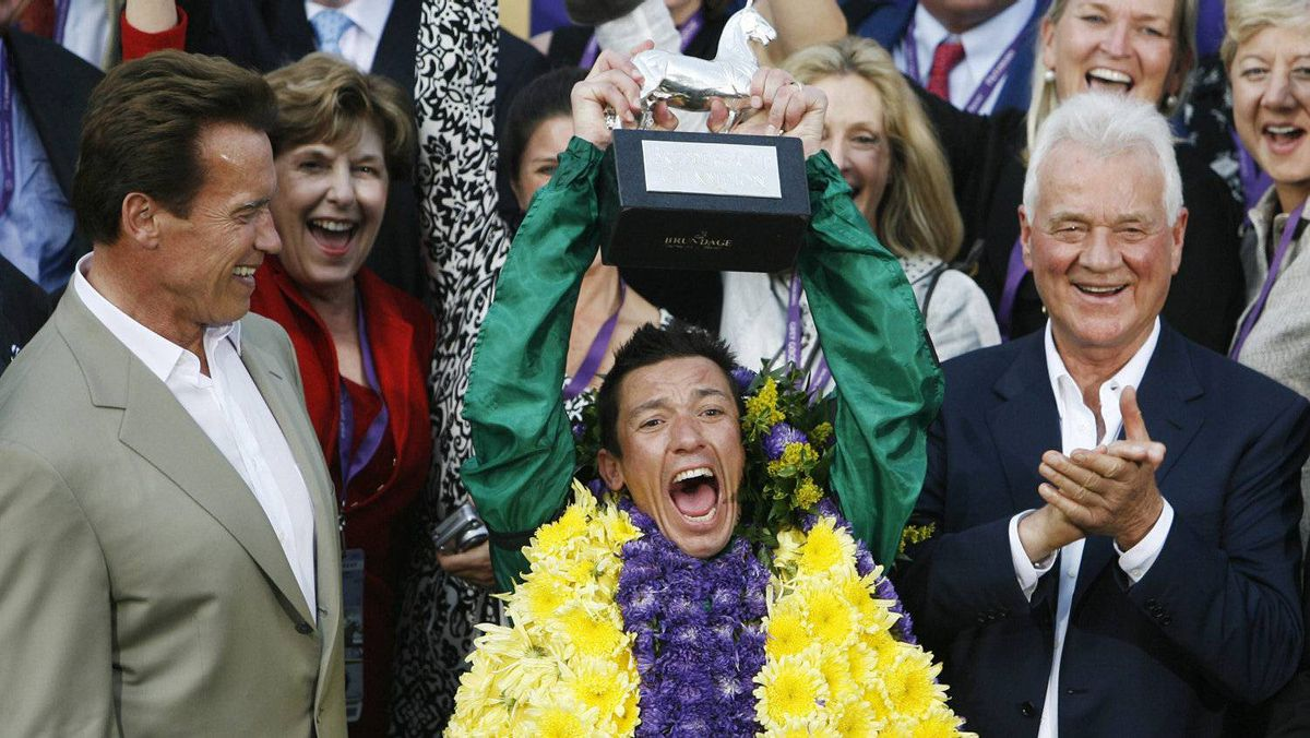 Jockey Lanfranco Dettori celebrates with the trophy after winning the Breeders' Cup Classic with Horse Raven's Pass beside Frank Stronach (R) and Governor of California Arnold Schwarzenegger (L) at Santa Anita Park in Arcadia, Calif, in October, 2008.