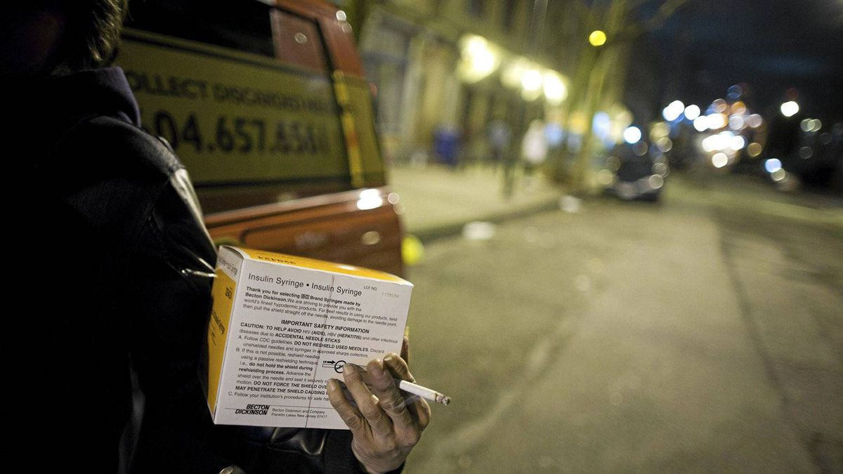 An intravenous drug user holds a box of syringes she received after approaching the Mobile Needle Exchange van in the Downtown Eastside in Vancouver, British Columbia, Thursday, March 1, 2012.