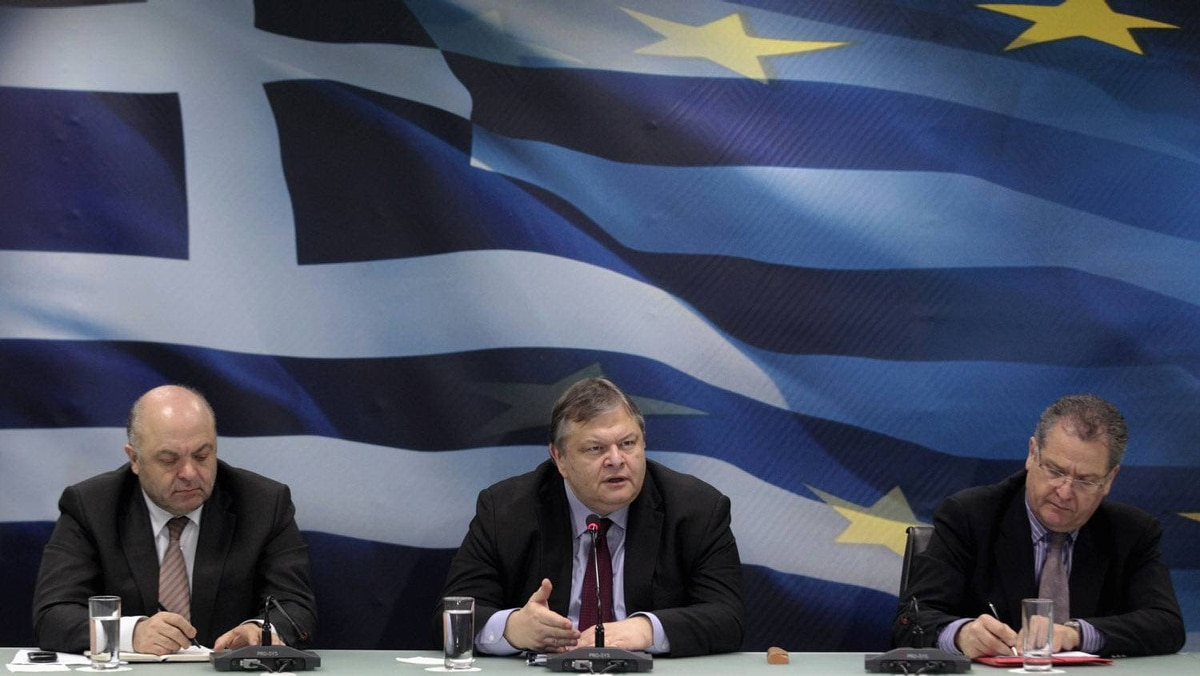 Greece's Finance Minister Evangelos Venizelos, centre, addresses reporters during a news conference in Athens after the country reached a second bailout agreement as economic adviser George Zanias, left, and deputy finance minister Pantelis Economou keep notes.