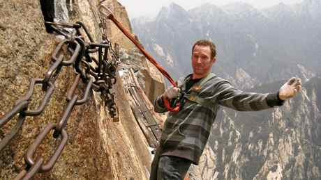 Robin Esrock puts his trust in the rope on the plank path, with a 1000m drop below Eastern China Yellow Mountains