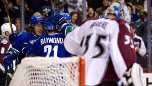 Vancouver Canucks' David Booth, from left, Mason Raymond and Ryan Kesler celebrate booth's goal as Colorado Avalanche goalie Jean-Sebastien Giguere looks on during the first period of an NHL hockey game in Vancouver, B.C., on Wednesday February 15, 2012.