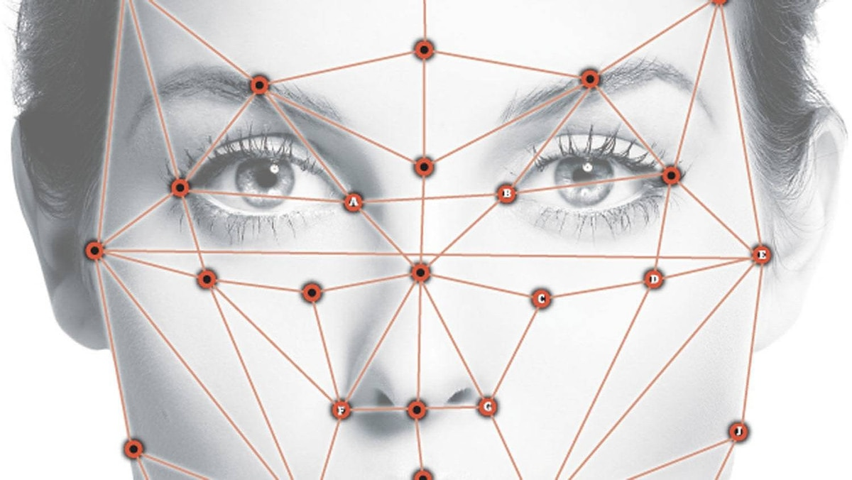An overlay depicts how facial recognition software pinpoints certain features and compares them to a database. The distance between the eyes and the shape of the cheekbone can be used to determine characteristics like sex and age.