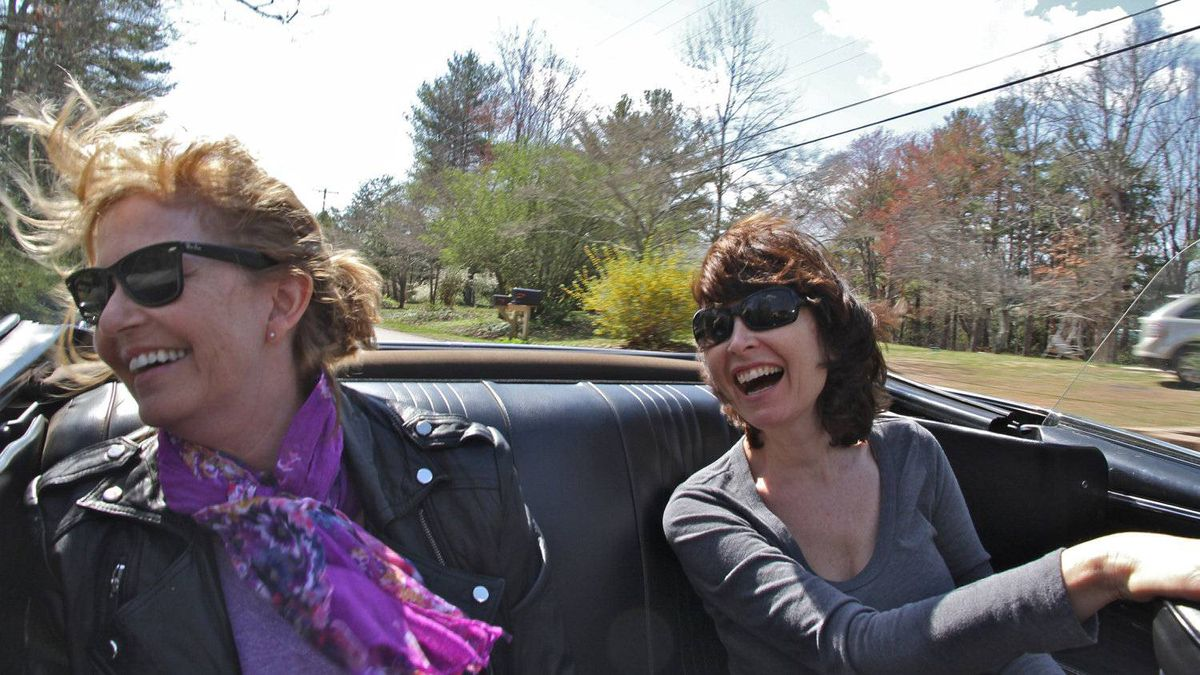 Peter Cheney's wife Marian (on the right) and her friend Robin Taber enjoying a top-down drive in a 1967 Pontiac GTO convertible.