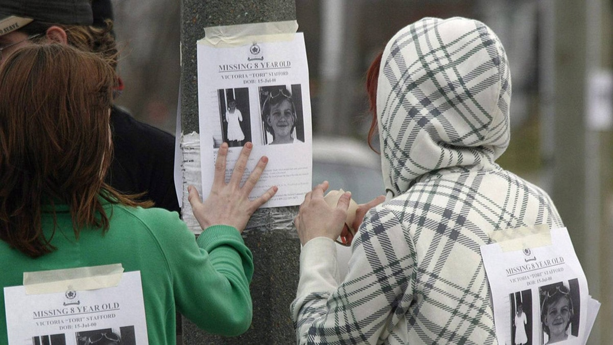 "Cassandra Craig and Shiloh Roth hang a poster for then missing Victoria ""Tori"" Stafford, 8, on a street corner in Woodstock, Ont. on Friday April 10, 2009."