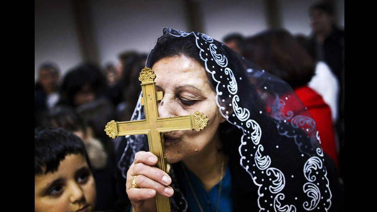 2nd Place Social Issues -- An Iraqi-Canadian kisses a holy cross during mass at the Our Lady of Good Counsel Church in Surrey December 12, 2010. The church has become the spiritual and geographical centre for Iraqi Christians in the area that have fled Iraqi because of their religious beliefs.