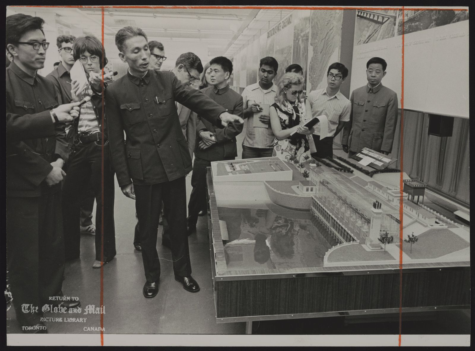 The notes transcribed from the back of this photograph are as follows: CANADIAN NATIONAL EXHIBITION Chinese Pavilion (Mr. Liu, interpreter, and Mr. Lu, deputy head of the exhibition delegation, looking at a model of a pumping station.)