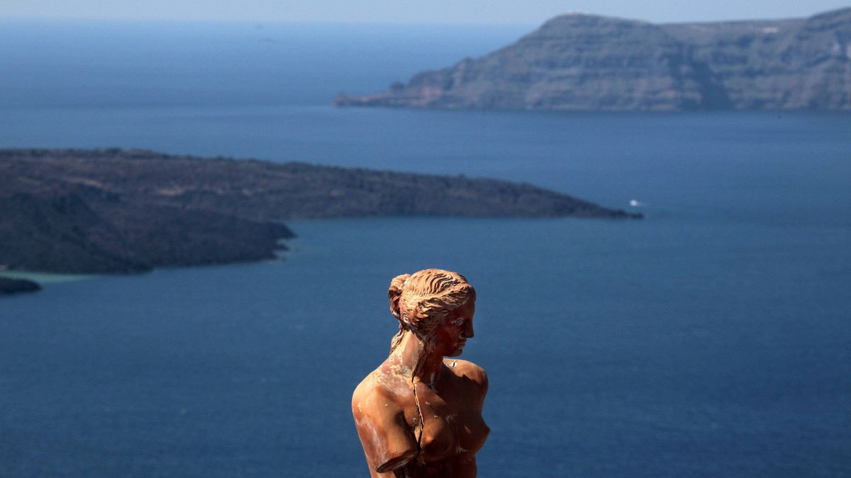 A replica of the ancient statue of Goddess Aphrodite of Milo is seen behind volcanic islets seen from the island of Santorini in the Aegean Sea, March 15, 2012.