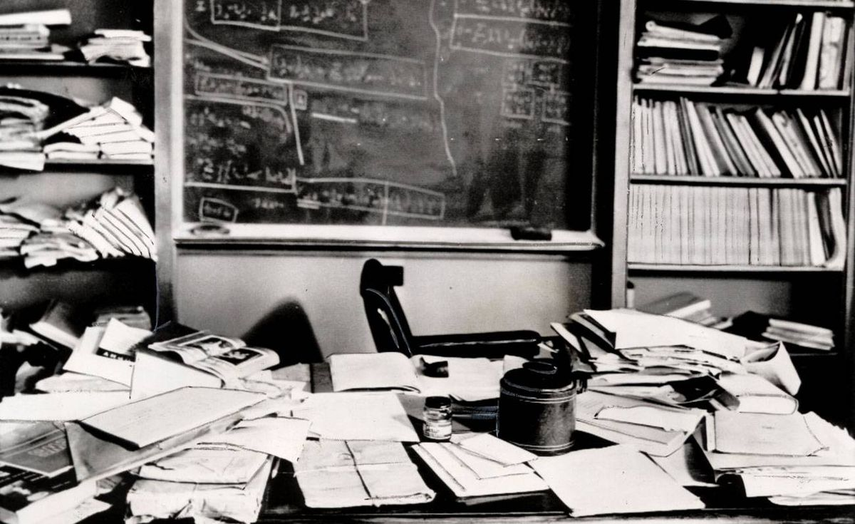 Familiar Pipe An Open Book A Cluttered Desk And Blackboard Covered With Mathematical
