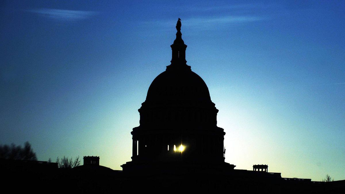 The Captiol dome is seen silhouetted against the rising sun in Washington
