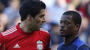 Liverpool's Luis Suarez (L) looks at Manchester United's Patrice Evra (R) during their English Premier League soccer match at Anfield in Liverpool, northern England October 15, 2011. REUTERS/Phil Noble