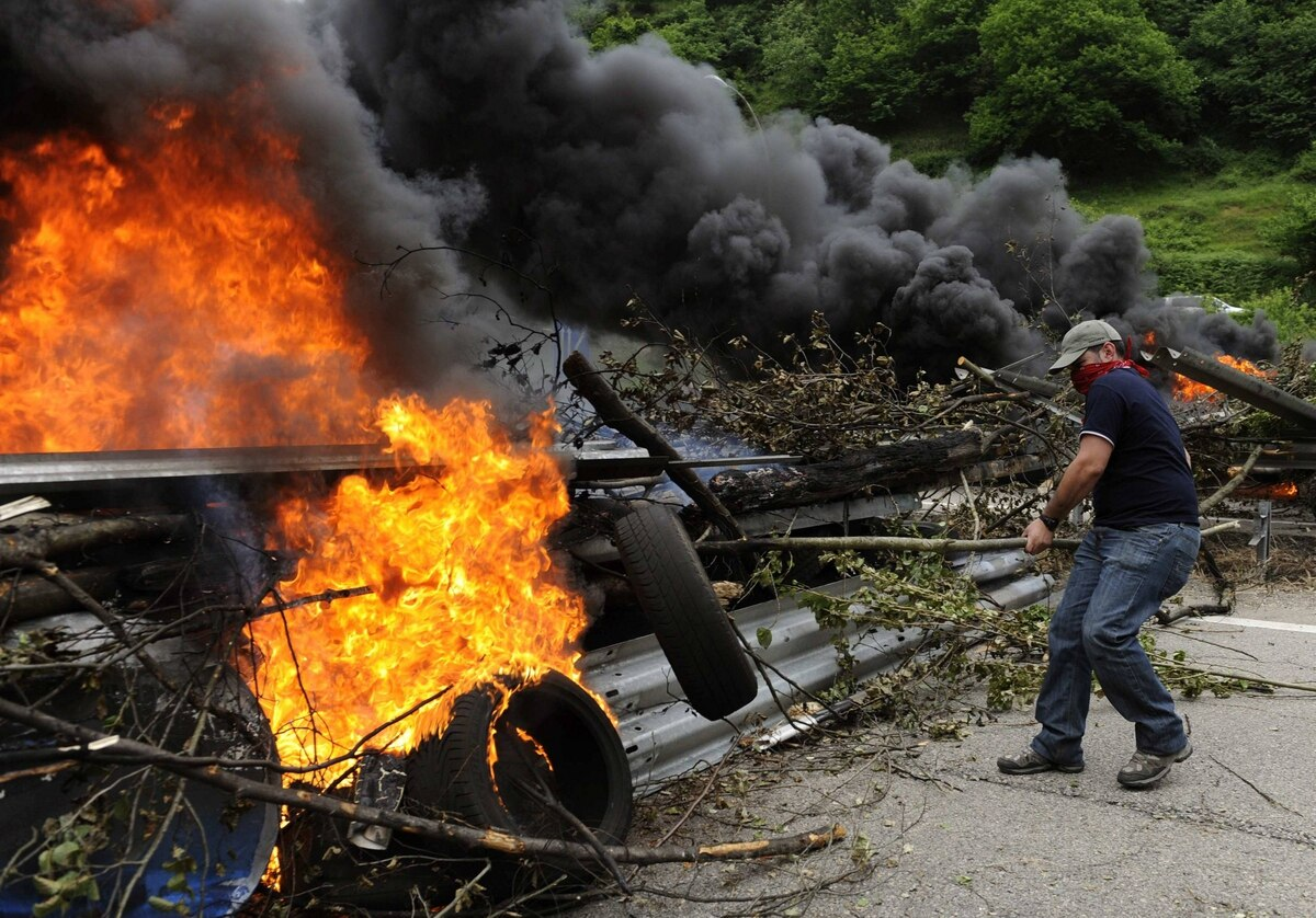 A striking coal miner places a burning tyre onto a barricade on the A-66 motorway to protest against the government's spending cuts in the mining sector, in Campomanes, near Oviedo, northern Spain.