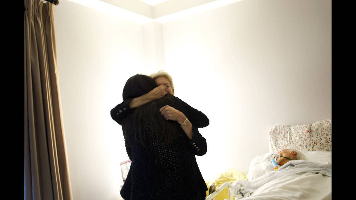 Basia Hoffman hugs Kensington Hospice social worker Maxxine Rattner during a visit with her mother, Andrée Hoffman, during her stay at Kensington Hospice in Toronto on Feb. 8, 2012.