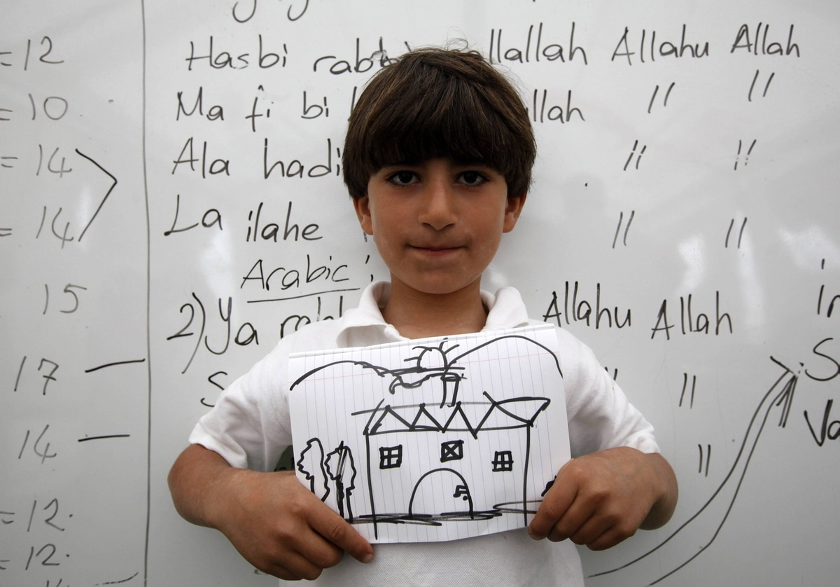 Cemil Hicazi, 10, a Syrian refugee, shows a drawing of his dream home during a class at a school for refugee children at Boynuyogun refugee camp in Hatay province near the Turkish-Syrian border.