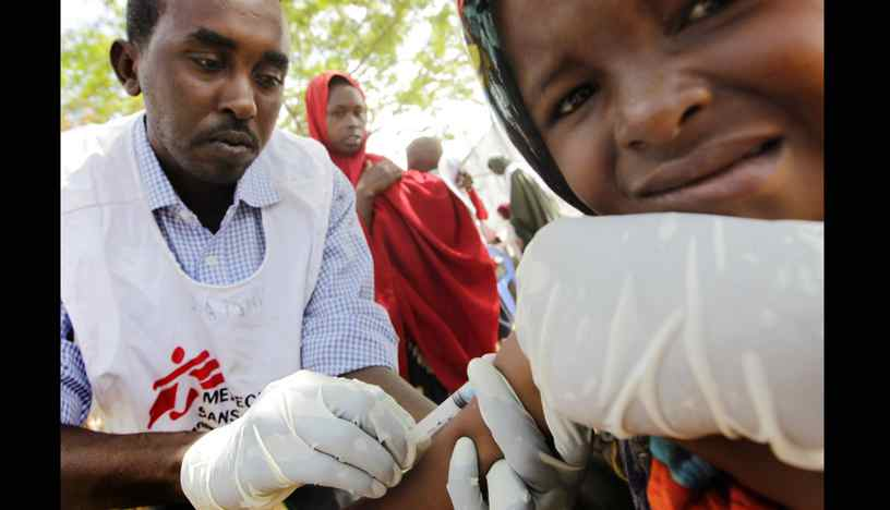 A child is looked at my an MSF worker during screening and measles vaccination clinic inside a section of the large Tarabunka camp.