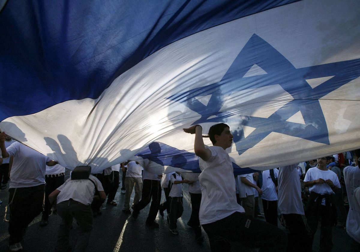 Israeli youths dance under a huge national flag during a parade marking Jerusalem Day in Jerusalem May 20, 2012.