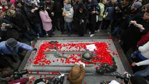 People lay poppies on the Tomb of the Unknown Soldier following Remembrance Day ceremonies at the National War Memorial in Ottawa November 11, 2011.