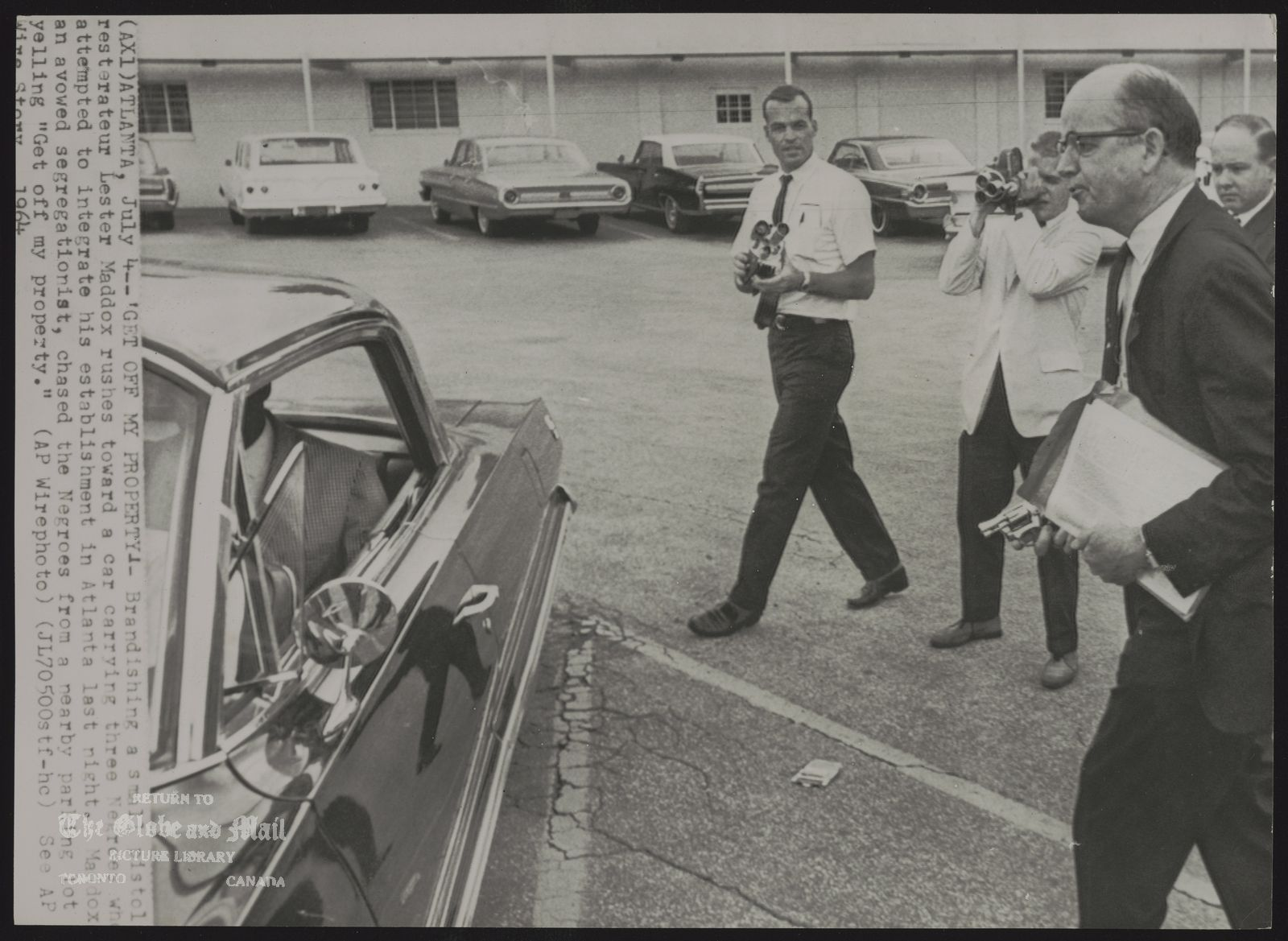 INTEGRATION (AX1) ATLANTA. July 4--'GET MY PROPERTY' --Brandishing a small pistol restauranteur Lester Maddox rushes toward a car carrying three Negroes who attempted to integrate his establishment in Atlanta last night. Maddox, an avowed segregationist, chased the Negroes from a nearby parking lot yelling