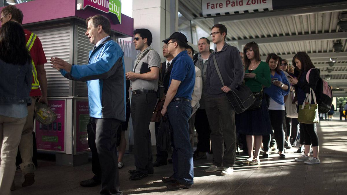 A TransLink employee directs commuters to lineup for the special bus service at the Commercial-Broadway SkyTrian Station after a service disruption. The transit company is prepared to introduce a gas tax but is waiting for mayoral approval.