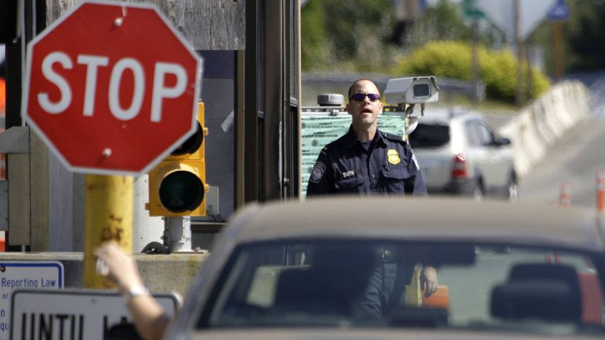 A U.S. Customs and Border Protection officer looks toward a car coming toward at the border crossing between the U.S. and Canada, in Blaine, Wash.