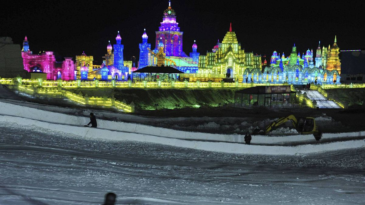 A snow slope near ice sculptures during the lights testing period of the 13th Harbin Ice and Snow World in Harbin in China.
