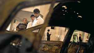 Israelis are seen through a burned car after a rocket fired from Gaza landed in Ashdod October 29, 2011. Israel's air force bombed an Islamic Jihad base in the southern Gaza Strip on Saturday, killing a commander and four munitions experts from the Palestinian faction, officials on both sides said.