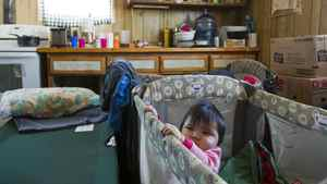 Ten-month-old Mylee stands in her crib in her home in Attawapiskat, Ont., Dec. 17, 2011. There are no plumbing or sanitary facilities in her residence.