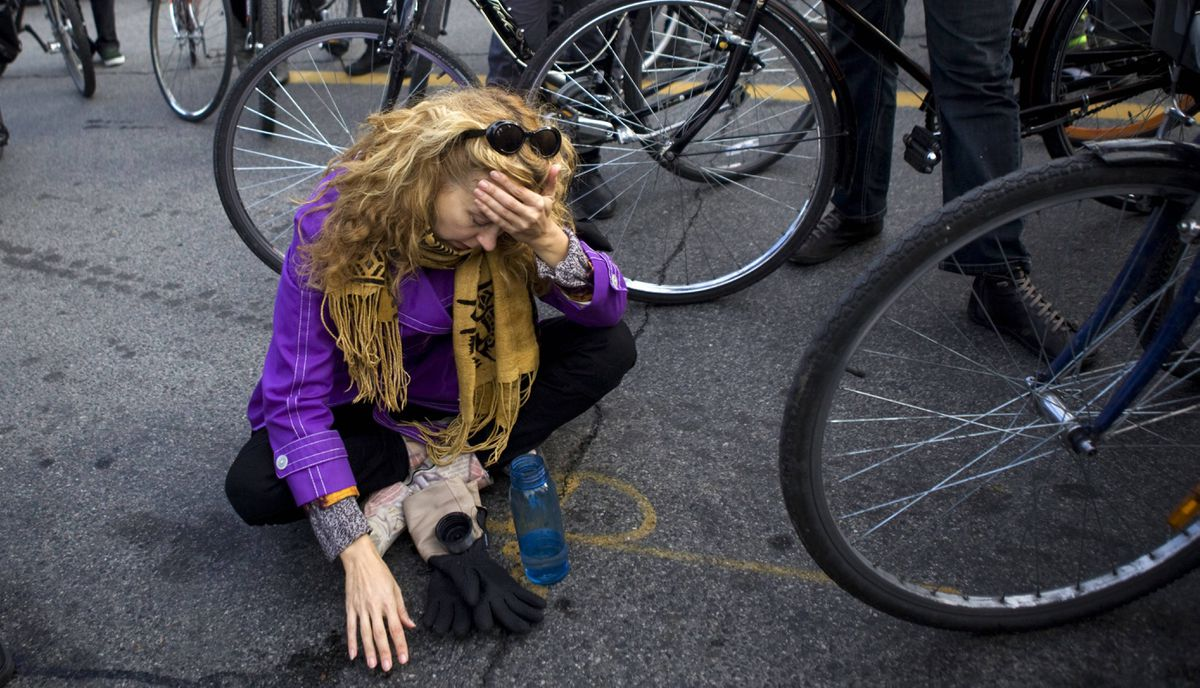 A woman sits on the ground at the end of a memorial ride on Monday, November 14, for pregnant cyclist Jenna Morrison, who was recently killed after being struck by a truck at Sterling and Dundas in Toronto.