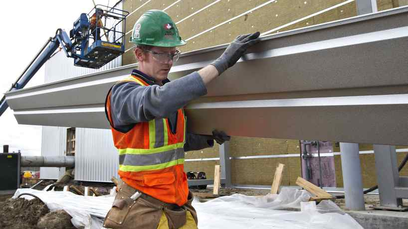 Temporary foreign worker Brian O'Donnell, from Ireland, carries a sheet of cladding while working on the construction of a new police station in Edmonton on April 30, 2012. In Alberta's stretched labour market, some employers have had to turn to overseas labour.