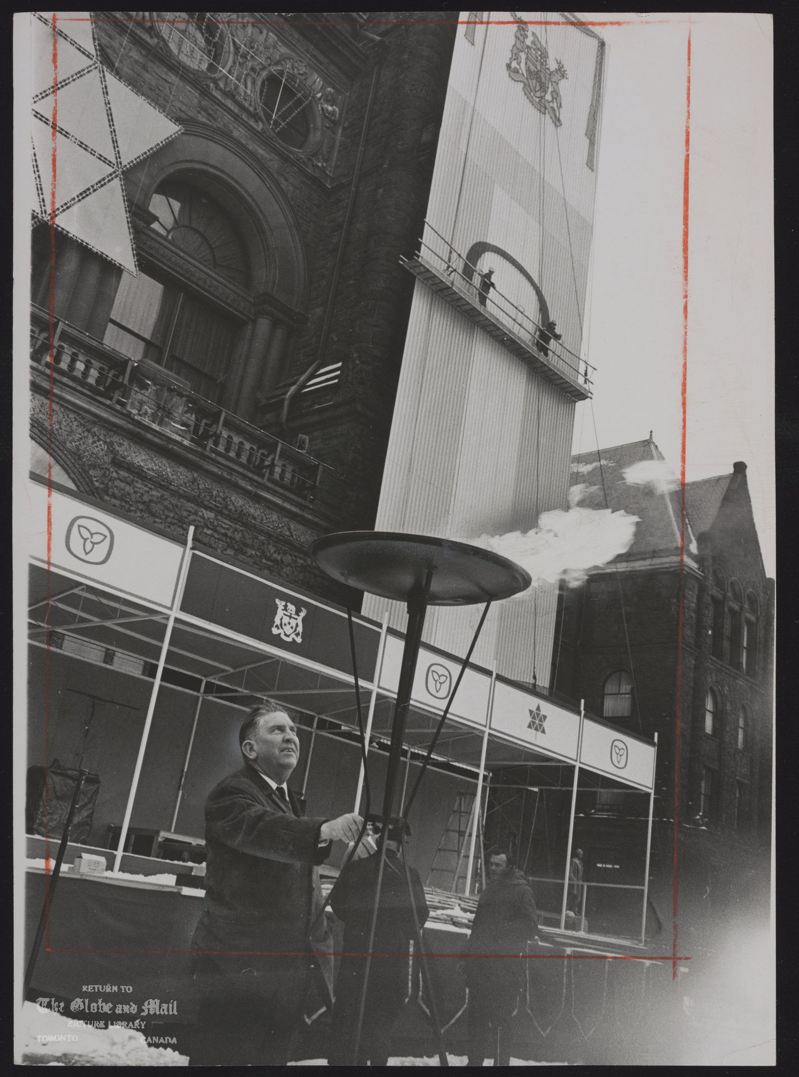 The notes transcribed from the back of this photograph are as follows: CANADA dominion Centennial J. B. Donaldson, tests perpetual flame that will be lit at Queen's Park on New Year's Eve while behind him workers decorate building for Saturday night's Salute to '67
