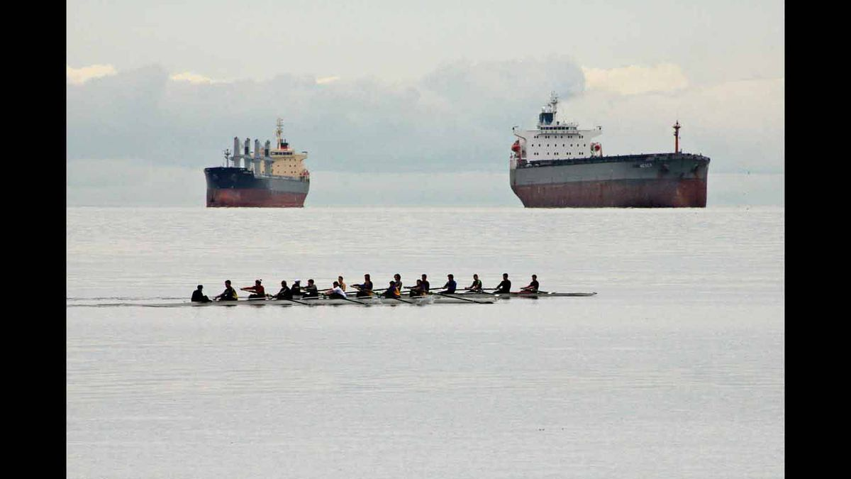 The rowers seem insignificant compared to the gigantic tankers.