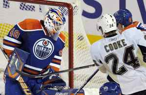 Edmonton Oilers' goalie Devan Dubnyk, left, watches the puck go into the net for a goal as Pittsburgh Penguins' Matt Cooke looks on during the third period of their NHL hockey game in Edmonton, January 14, 2010.