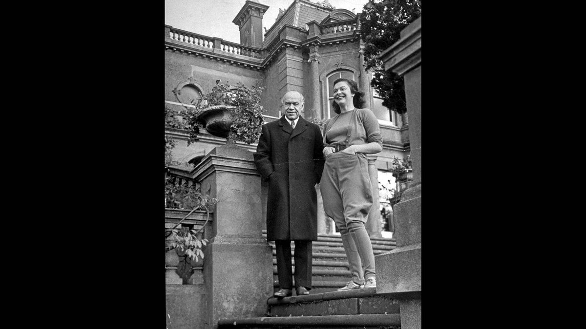 Lord Beaverbrook, publisher of LONDON DAILY EXPRESS newspaper, posing w. his daughter Mrs. Drogo Montagu, in front of his country home.