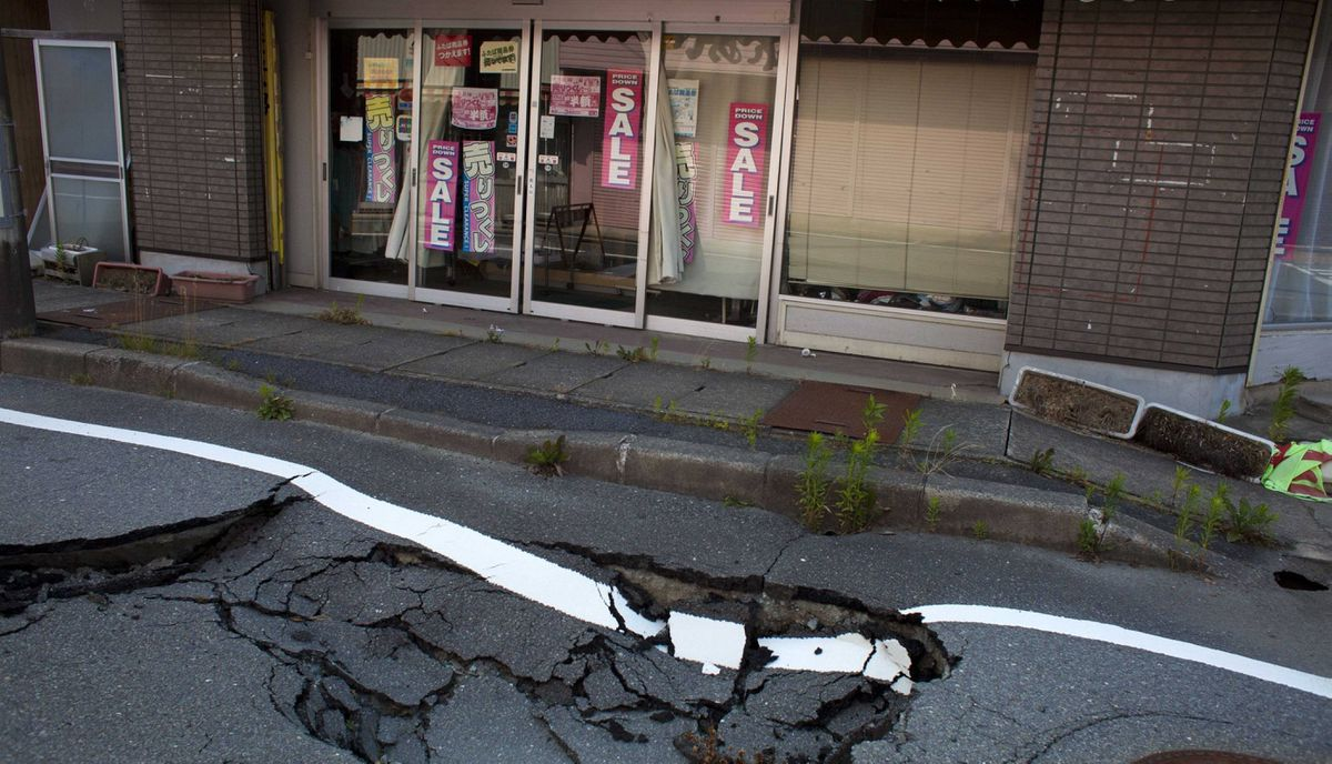 An earthquake-damaged street sits in front of an abandoned shop in the town of Naraha, inside the 20-kilometer exclusion zone around the Fukushima Daiichi nuclear plant July 16, 2011 . A year after the Tsunami, cleanup has begun, but experts say areas inside the nuclear exclusion zone will be difficult to decontaminate.