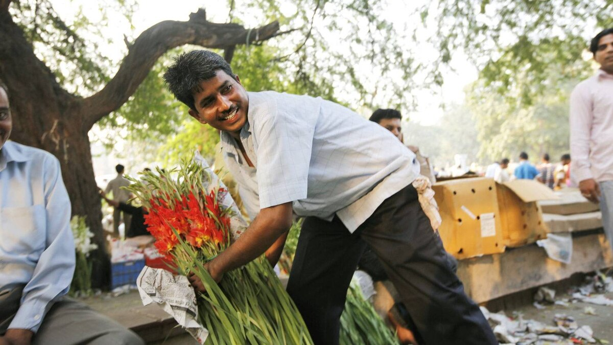 Mr. Verma buys fresh flowers at a flower market to sell at his stall.