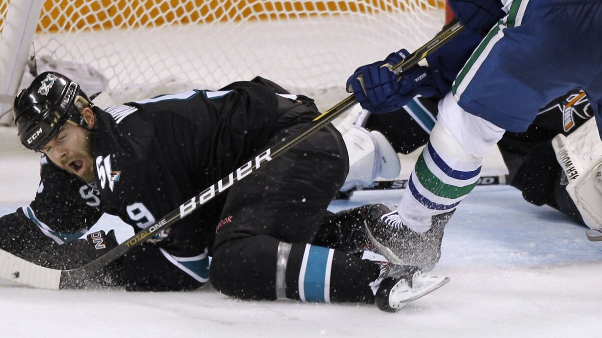 San Jose Sharks Ian White reacts after he was knocked down by Vancouver Canucks Kevin Bieksa.. REUTERS/Mike Blake