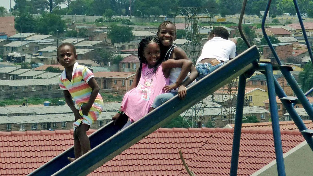 Kids play in a new Soweto park in Diepkloof Extension, near hostels that once saw horrific political violence.