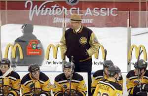 Boston Bruins head coach Claude Julien, rear, coaches his team during the second period of the New Year's Day Winter Classic NHL hockey game against the Philadelphia Flyers on an outdoor rink at Fenway Park in Boston, Friday, Jan. 1, 2010. (AP Photo/Charles Krupa)