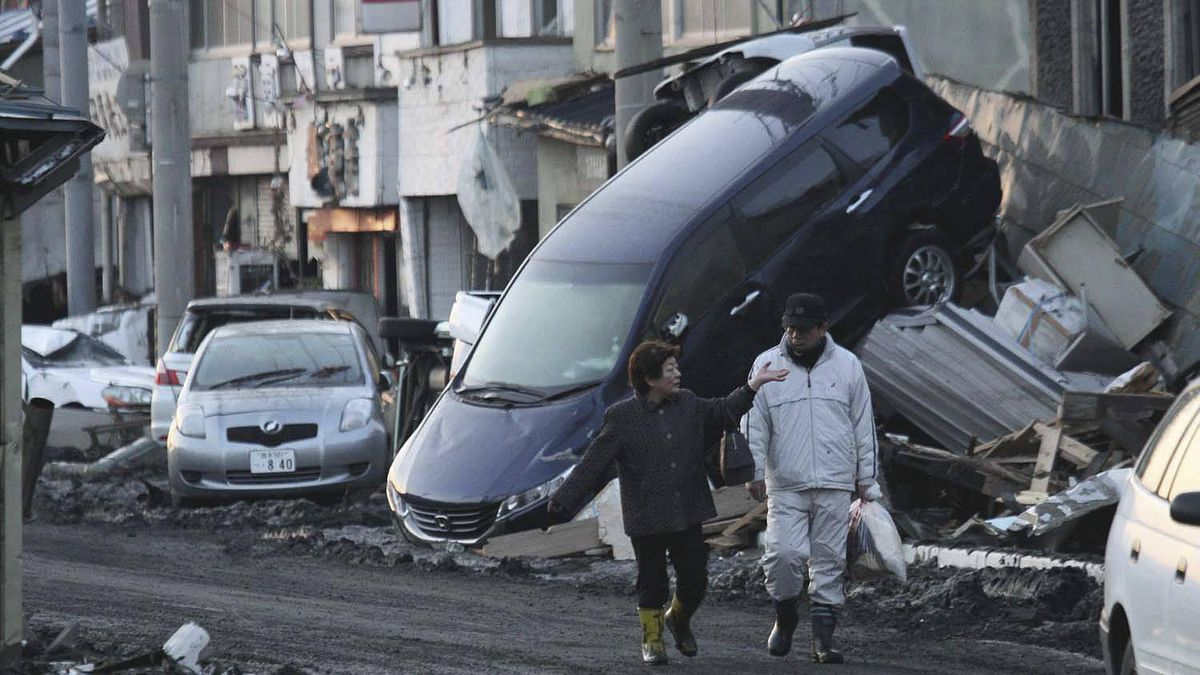 People walk by a car got stuck into a building in Miyako, Iwate Prefecture (state), northern Japan, Saturday morning, March 12, 2011, a day after a strong earthquake-triggered devastating tsunami hit the area.
