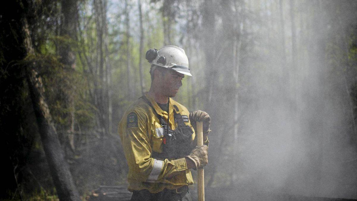 Firefighter Jason McAleenan puts out hot spots near Slave Lake, Alta.