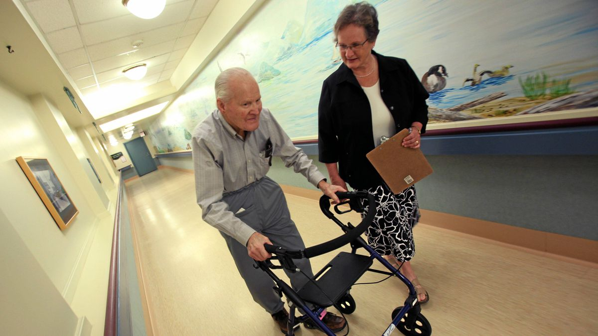 Ministry of Healthy Living and Sport's, Dr. Vicky Scott, walks with Broadmead Care Society resident Gene Seward through a hallway wearing his track pants with a built in hip protector. A soft padded energy absorbent padding worn to prevent hip fractures.