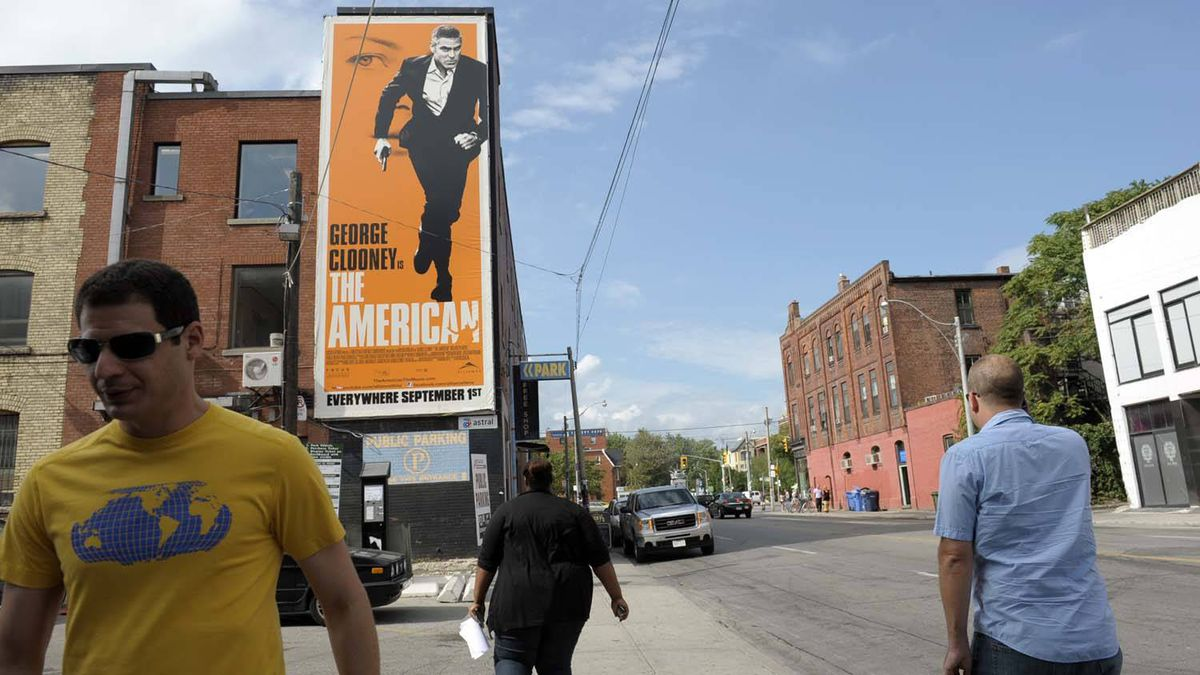 A billboard on the side of a building near the corner of Queen St. West and Peter St. in downtown Toronto promotes a film, The American.