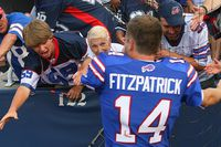 Ryan Fitzpatrick #14 of the Buffalo Bills celebrates with fans after defeating the New England Patriots at Ralph Wilson Stadium on September 25, 2011 in Orchard Park, New York. Buffalo won 34-31. (Photo by Rick Stewart/Getty Images)