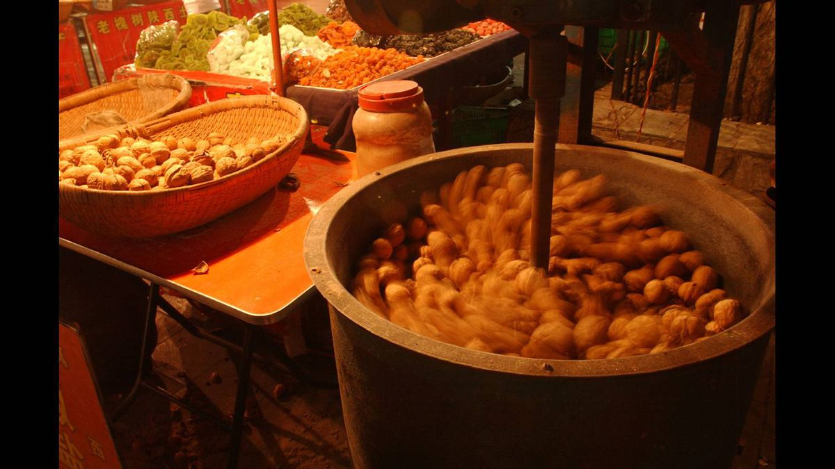 This photo of nuts being heated was shot at a night market in Xi'an, China . Shot at 1/4 second shutter speed only the objects not moving appear sharp. The nuts are moving slowly in the bin and appear blurred.