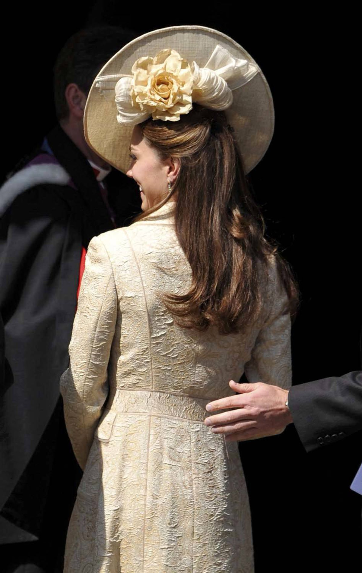 Kate takes a low-key approach for the wedding of Zara Phillips on July 30, wearing a brocade coat from 2006 and a hat by Gina Foster Millinery.