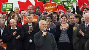 NDP Leader Jack Layton, backed by his supporters, addresses a crowd in Winnipeg on April 27, 2011.